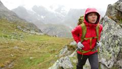 Hiking - woman hiker backpack trekking in rain on mountain Stock Footage