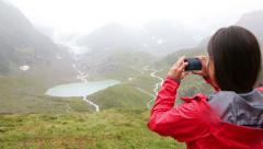 Woman taking picture with smart phone, Swiss alps Stock Footage