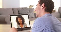 Multi-ethnic friends webcamming on laptop - stock footage