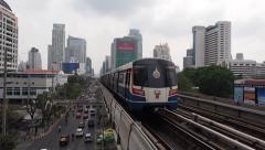 SkyTrain Metro Passing on Bridge Next to Busy Street, Bangkok, Thailand Stock Footage