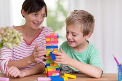 young mother helping her son build a tower - stock photo