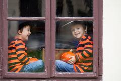 two cute boys, sitting on a window with jack-o-lantern - stock photo