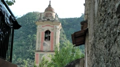 Europe Italy Liguria Airole village 020 baroque church tower at end of alley Stock Footage