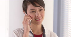 Attractive Asian doctor talking on smartphone Stock Footage