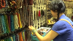Young lady picking and choosing handmade prayer beads necklaces in the store Stock Footage