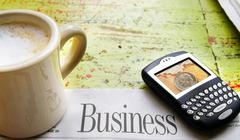 cup of coffee, cell-phone, and newspaper business section - stock photo