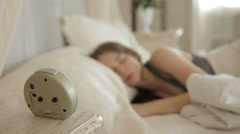 Beautiful young woman turns off the alarm, turns over and continues to sleep. - stock footage