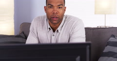 African man watching the game on TV Stock Footage