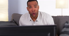 Black man watching the game on TV Stock Footage