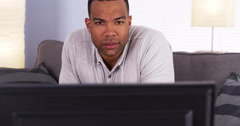 African man watching show on TV Stock Footage