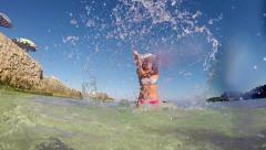 Slow motion: girl with straw hat splashing water toward camera on summer beac Stock Footage