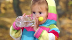 The child is drinking mineral water.Little girl is drinking water in nature. Stock Footage