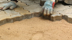 Worker installing old cobblestone block for build floor ground Stock Footage