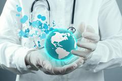 Doctor holding  world globe and splash colors in her hands Stock Illustration