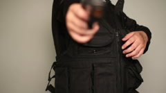 Child holstering a realistic gun into tactical vest - stock footage
