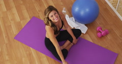 Happy healthy young woman smiling on workout mat - stock footage
