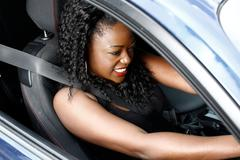 young black woman driving in safety seat belt - stock photo