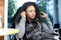 Curly black woman listening music using headphone Stock Photos
