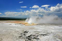 Geyser basin erupts against blue sky Stock Photos
