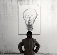 businessman looking at light bulb in art frame on the wall as concept - stock illustration