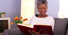 Happy senior black woman looking though photo album - stock footage