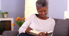 Mature Black woman enjoying a good book Stock Footage
