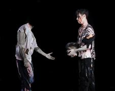 Two male zombies, one giving the head to the decapitated one's body Kuvituskuvat