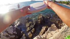 Playing frisbee at seashore rocks pov, slow motion Stock Footage