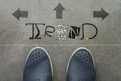 hand drawn trend design word on front of business man feet as concept - stock illustration