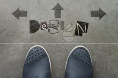 hand drawn design design word on front of business man feet as concept - stock illustration