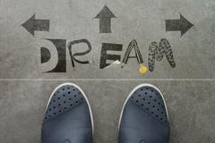 hand drawn dream  design word on front of business man feet as concept - stock illustration