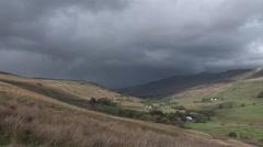 Dark storm clouds and a rainbow over the Cumbrian fells near Aisgill Stock Footage