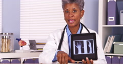 African senior doctor talking to camera with tablet and xray Stock Footage