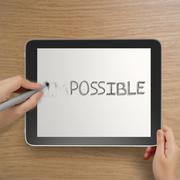 Hand changing the word impossible to possible with stylus eraser on tablet co Stock Photos