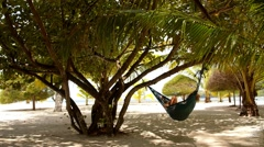 Woman Resting in Hammock on a Beach near the Sea. Stock Footage