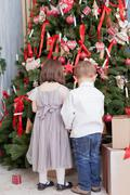 children decorate a christmas tree for christmas - stock photo