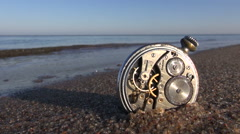 Time and sea concept - analog pocket clock on sea beach sand Stock Footage