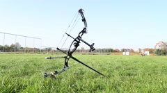 Bow and arrow lying on the field - stock footage