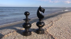 Two black retro chess pieces on summer sea  beach sand Stock Footage