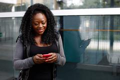 Young african woman reading a text message Stock Photos
