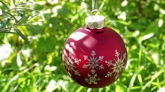 Red christmas ball on green summer background Stock Footage