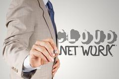 Businessman hand drawing  cloud network desogn word and diagram on the new co Stock Illustration