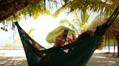 Woman Using Smart Phone Relaxing in Hammock. Stock Footage
