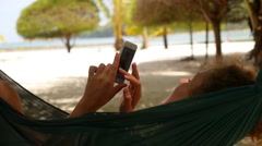 Relaxed Woman Using Smartphone in Hammock on Beach. Stock Footage