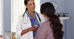 Black doctor explaining prescription medicine to female patient - stock footage