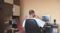 Ending phone conversation, man put headphones on play the movie watch on desktop Stock Footage