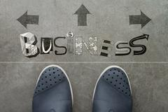 hand drawn business  design word on front of business man feet as concept - stock illustration