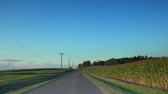 Driving back road next to corn field at dusk Stock Footage