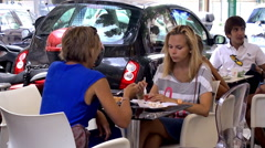 Two girls are eating a dessert at an outdoor cafe. Stock Footage