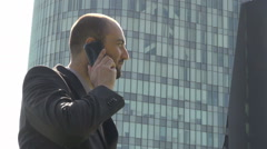 Business discussion on mobile phone, man talking and approving, outdoor office - stock footage